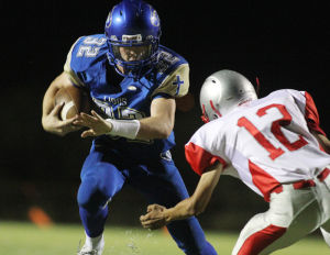 Pusch Ridge Vs Santa Cruz Football: Pusch Ridge Christian Academy's Connor Reilly throws out his arm to block a defender as he ran the ball in for a touchdown during the second quarter. The Lions shutout the Dust Devils 62-0. - Randy Metcalf/The Explorer