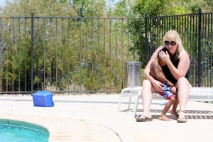 The Galloway Family: Kelli Galloway sits with her son Caden, 3, out by their pool. The family beats the heat and spends time together in the water. - Randy Metcalf/The Explorer