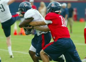 University Of Arizona: University of Arizona quarterback Matt Scott hands the ball off to Ka'Deem Carey during practice.  - Randy Metcalf/The Explorer