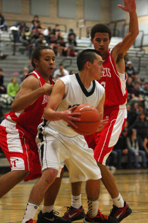 Mountain View Vs Tucson High Mens Basketball: Mountain View High School senior Miko Simental looks for an open man as two Tucson High players defend him Tuesday night. The Mountain Lions lost to the Badgers 60-56.  - Randy Metcalf/The Explorer
