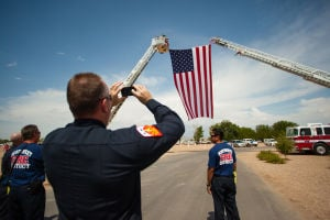 William Warneke Procession: Northwest Fire Department Captain Eddie Croy takes a photo of the large flag that was on display at the funeral for Granite Mountain Hotshot William Warneke. - J.D. Fitzgerald/The Explorer