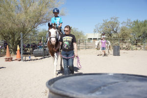 Horse Camp: Camp helper, Ashley Bruch, helps lead the horse Bella and rider Chad Burrous around the ring. By the end of the week some riders may be able to ride the horse with little or no help. - Hannah McLeod/The Explorer