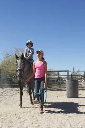 Horse Camp: Hannah Betton, a camp helper, leads the horse Chief with 8-year-old rider Frankie Delong. - Hannah McLeod/The Explorer