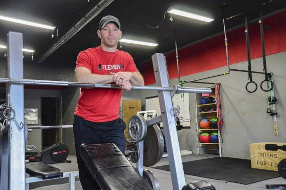 <p>Fletcher Fitness co-owner Dallas Fletcher stands behind equipment in the Valparaiso gym that opened in 2015. The location has become a favorite spot for many village residents. (Staff Photo by Michael Wunder)</p>