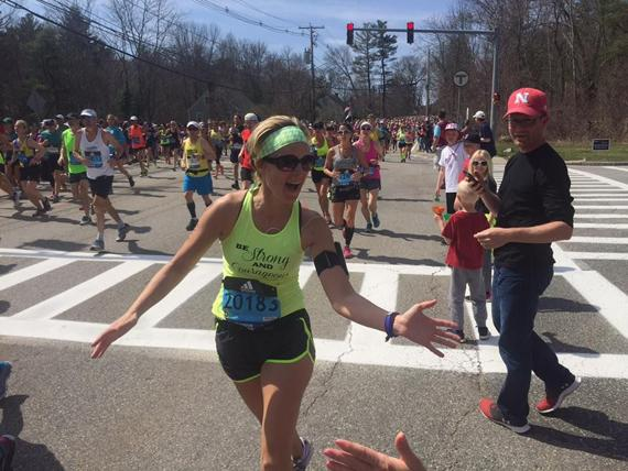 <p>HIGH FIVE: Melinda Bentjen takes a moment during the Boston Marathon to give high-fives to onlookers. Bentjen ran the 2016 race in four hours. (Photo Courtesy of Melinda Bentjen)</p>