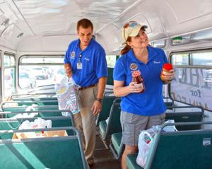 <p>Jordan Ottoman, president of the Wahpeton Rotary Club, and Darcie Huwe, member of Wahpeton Rotary, help organize food donations brought in to the Fill the Bus campaign Thursday at Econofoods. The annual campaign by Wahpeton and Breckenridge Rotary Clubs help fill the food pantry at a time when donations are traditionally down.</p>