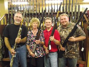Committee members (from left) Dave Olson, Roxanne Olson, Andrew Arnold and Tony Freeman show off a few of the more than 30 guns and other prizes that can be won by attending the event and buying raffle prizes.