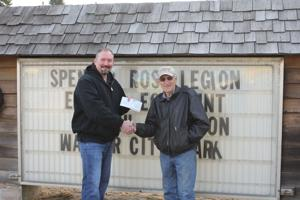 Pictured is Walker Mayor Jed Shaw (left) accepting the check from Carl Berg of Leech Lake Lumber.