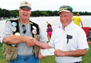 Bob Kennedy (left), chairman of the fishing contest, accepts a check for $500 from Eugene Gagnon of the Backus American Legion for the popular event.