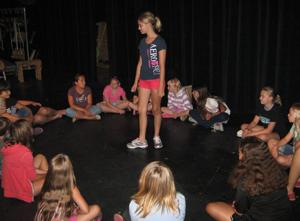 Madisyn Tyk (standing) leads a warm-up activity for theater camp.