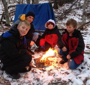 Carson Swanson (from left), parent Don Goff, Hunter Goff and Trevor Johnson learn how to start a fire.