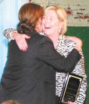 <p>Patti Souther (facing camera) hugs 2016 Chamber of Commerce Chairwoman Terri Braswell after Souther's State Farm agency was chosen as the 2015 Business of the Year at the chamber's annual meeting Thursday night, Jan. 28, 2016, in Monroe.</p>