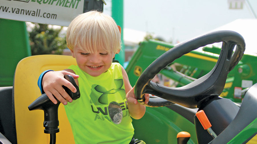 Maddyx Sieren, 3, checks out the big tractors