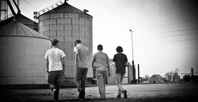 Four young workers walk toward bins