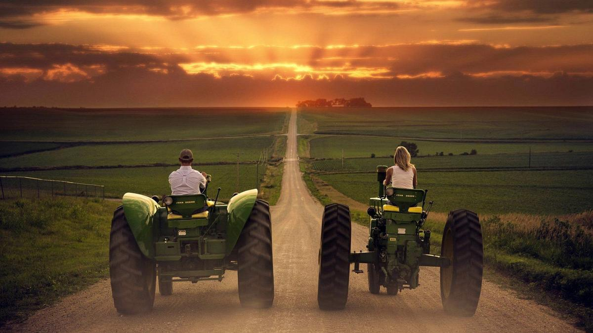 Farm couple riding down road on tractors