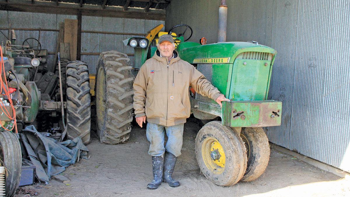 John Ernst stands with his John Deere 2520 tractor