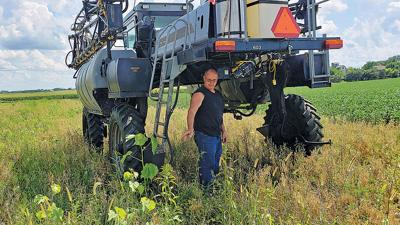 Jim Robbins stands with a Hagie high-chassis sprayer in a field.
