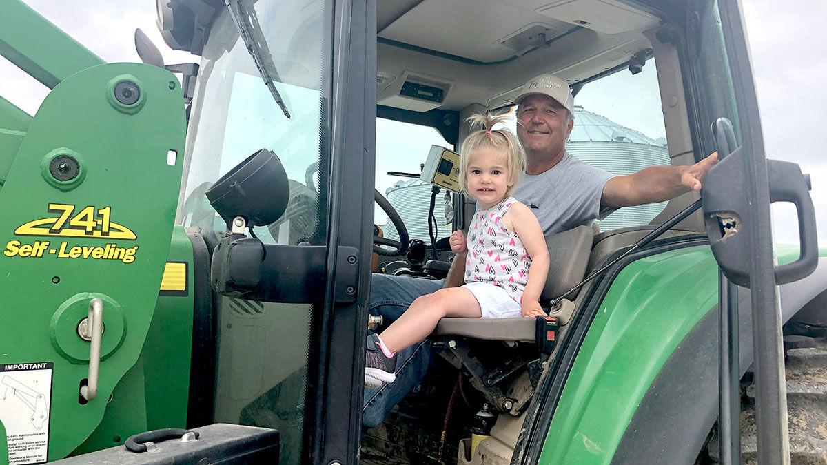 Bruce Mershon and his granddaughter, Maren, feed cattle