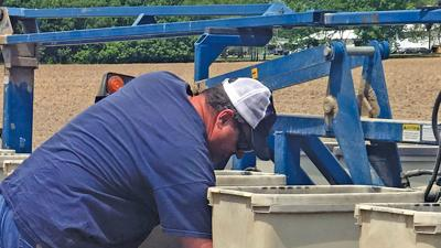Kelly Robertson checks seed in a planter