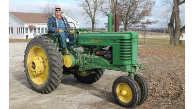 Galen Lowrey drives a 1950 John Deere A tractor