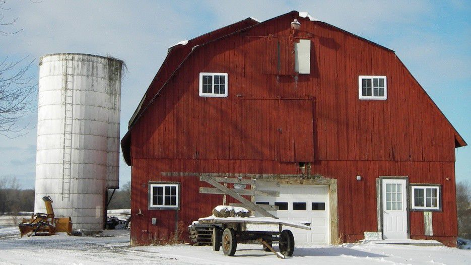 Barn with silo sits in snow