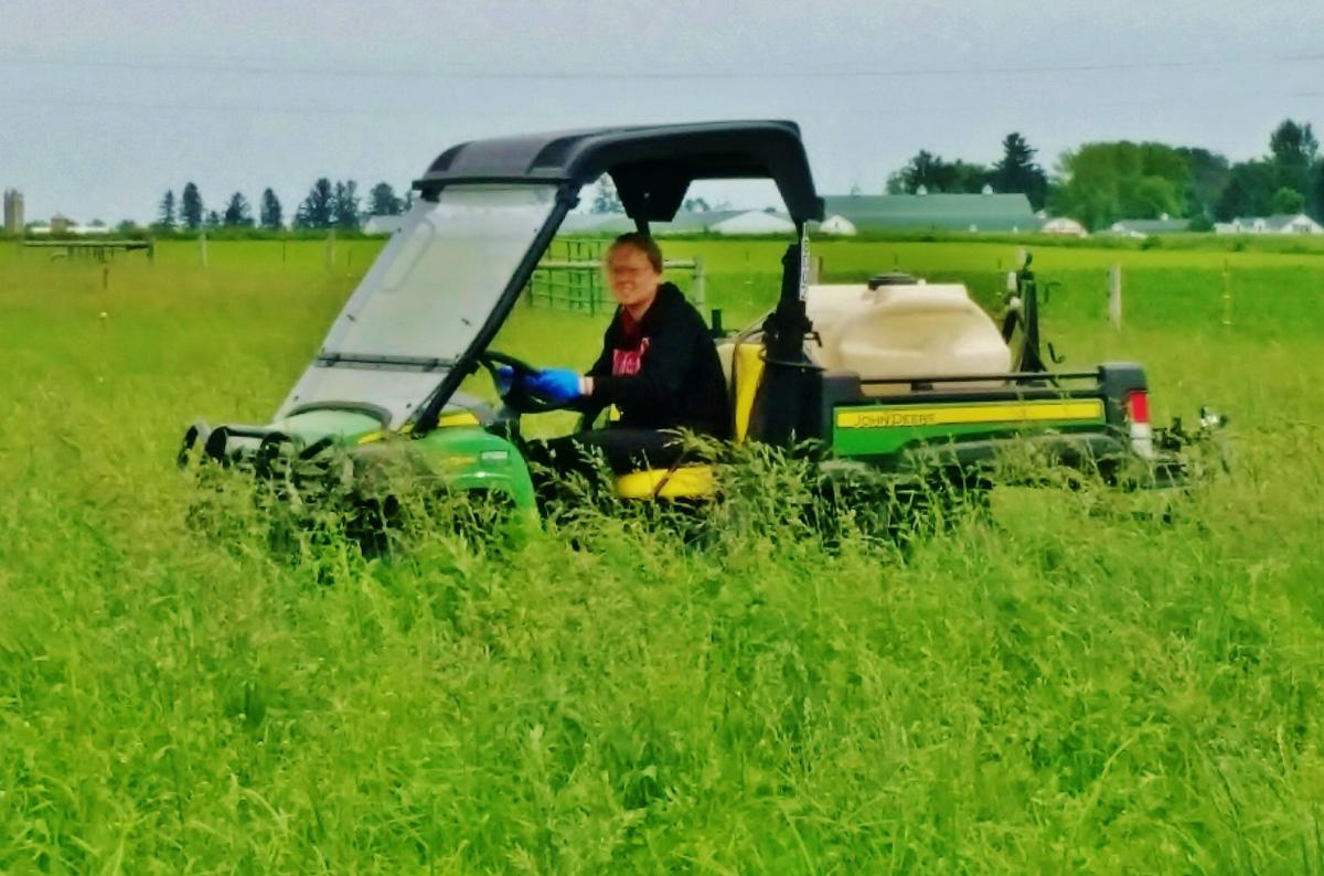 Mary Magnuson in field with sprayer