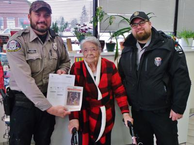 Wardens Joe Paul, left, and Nic Hefter pose with Florence Teeters,