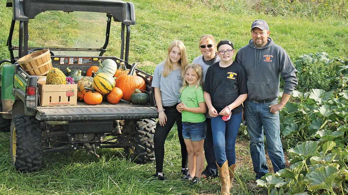 Schaer family poses with the pumpkin display