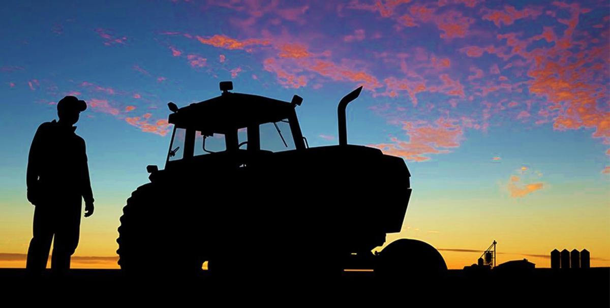 Farmer and tractor in field at sunset