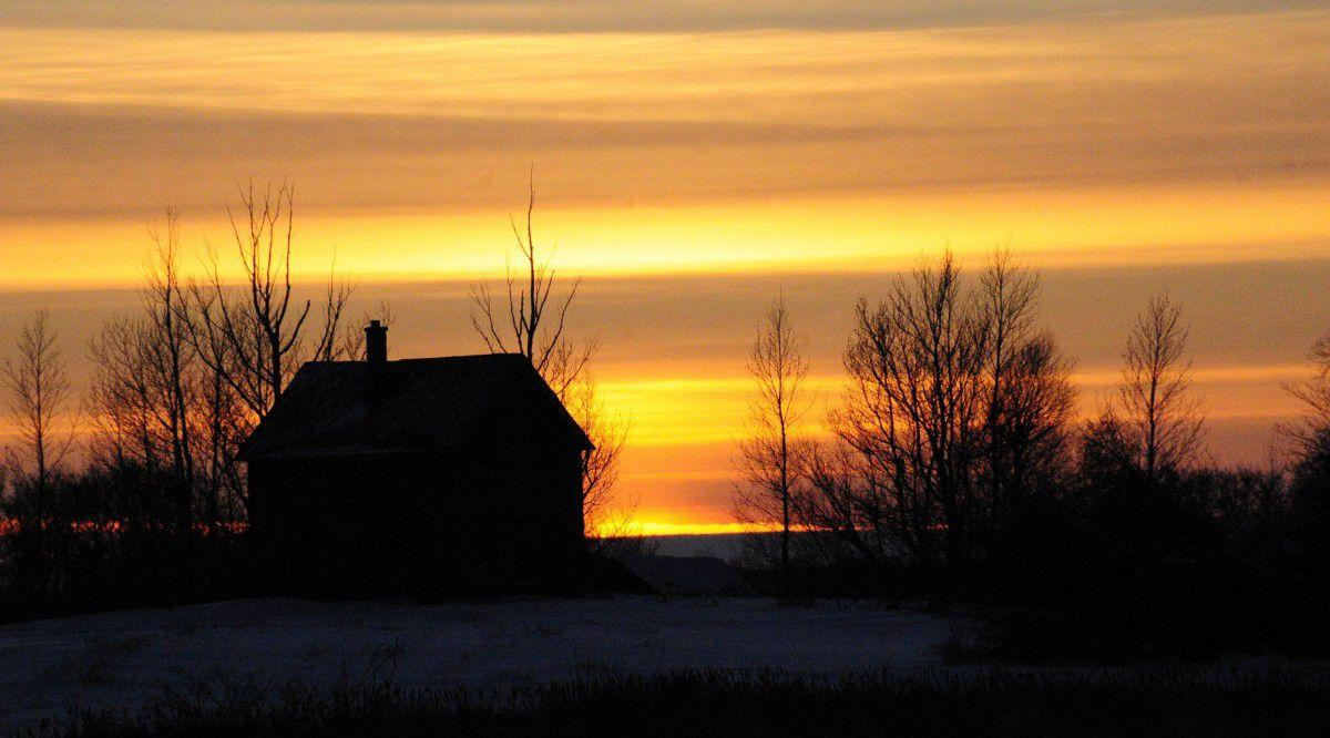 Sun sets on rural house