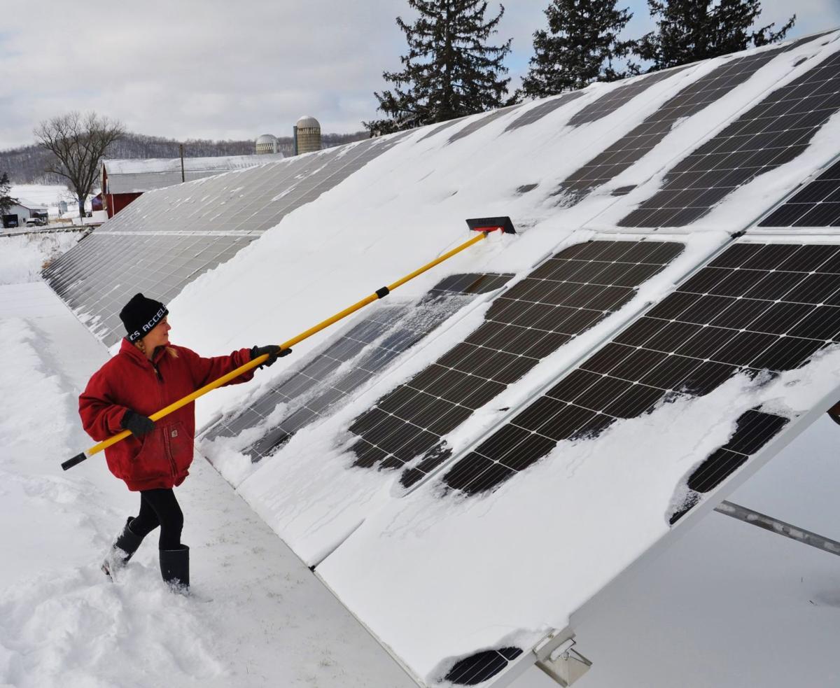 Joette Wolfe sweeps snow off solar panels