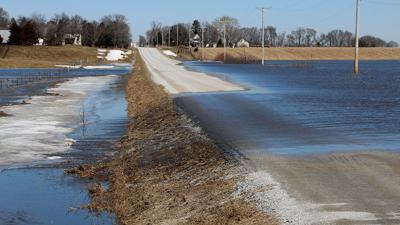 Rising waters from the Nishnabotna River flows over the road near Hastings.