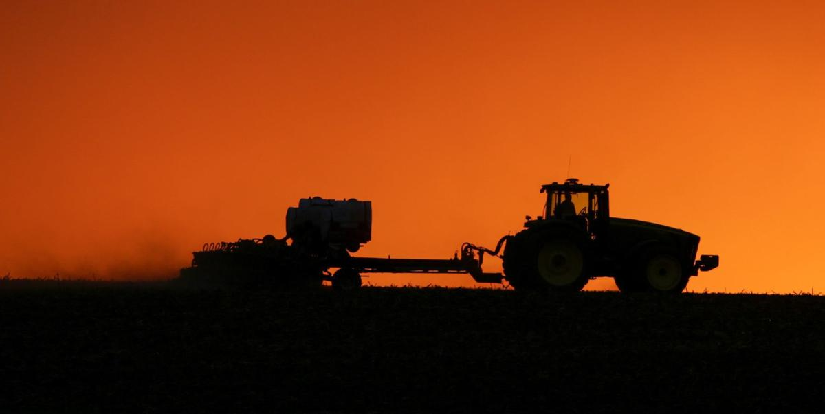 A farmer is silhouetted by the setting sun as he plants a field