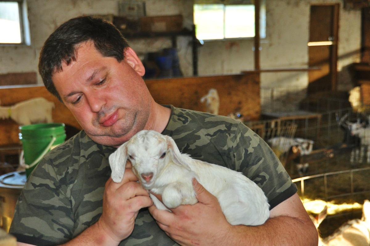 Jeff Puterbaugh shows one of this spring's goat kids.