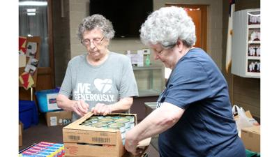Lorna Rebhuhn and Linda George pack boxes at their food pantry