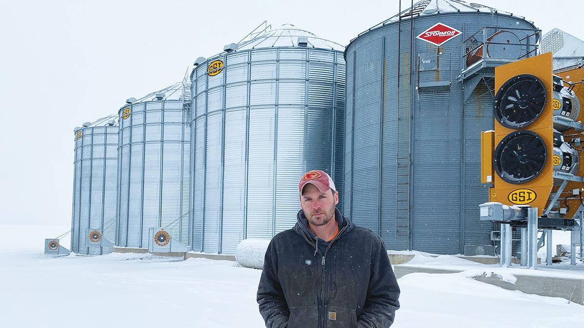 Ryan Vavroch stands in front of his grain bins