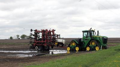 Delayed planting Tractor at edge of wet field