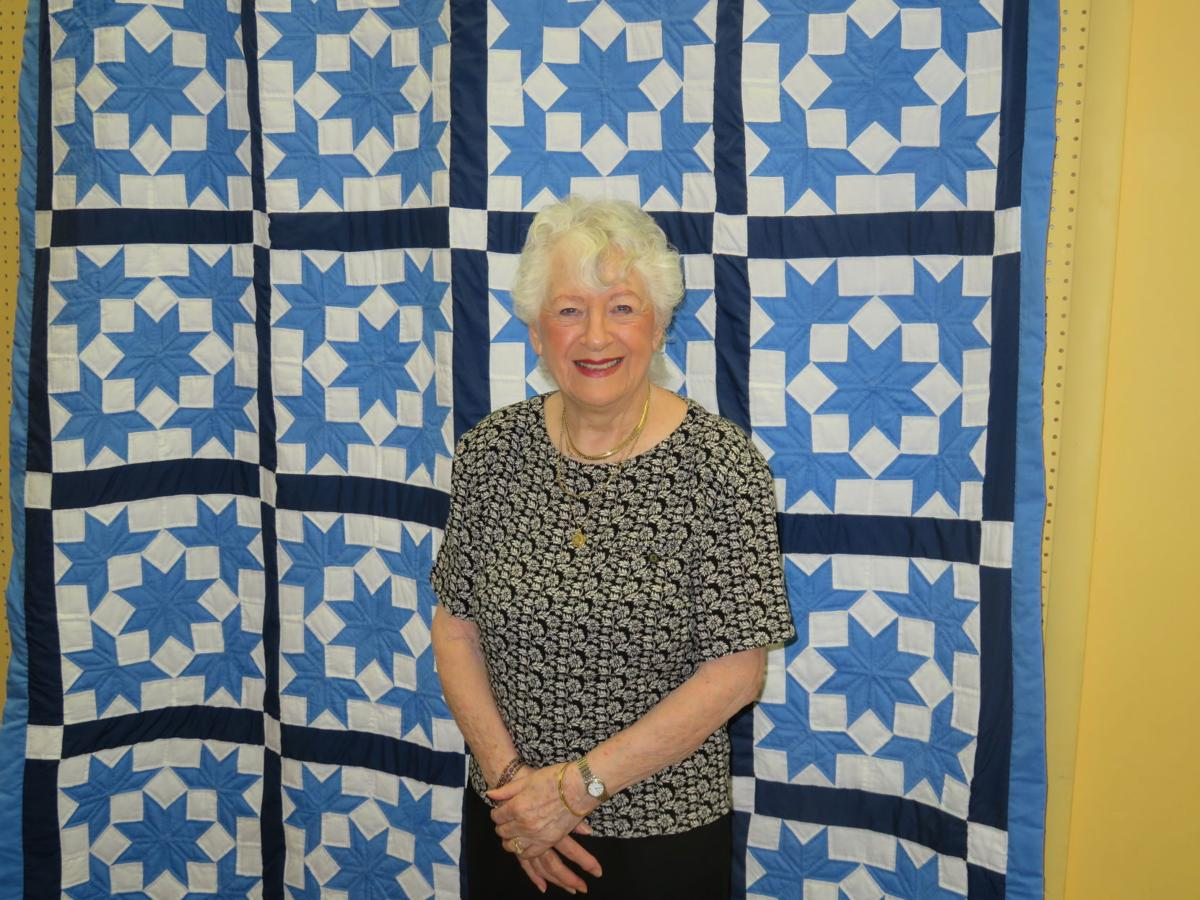 Ahwatukee resident Mina Brun poses with her quilt, which will be raffled off at the book sale.