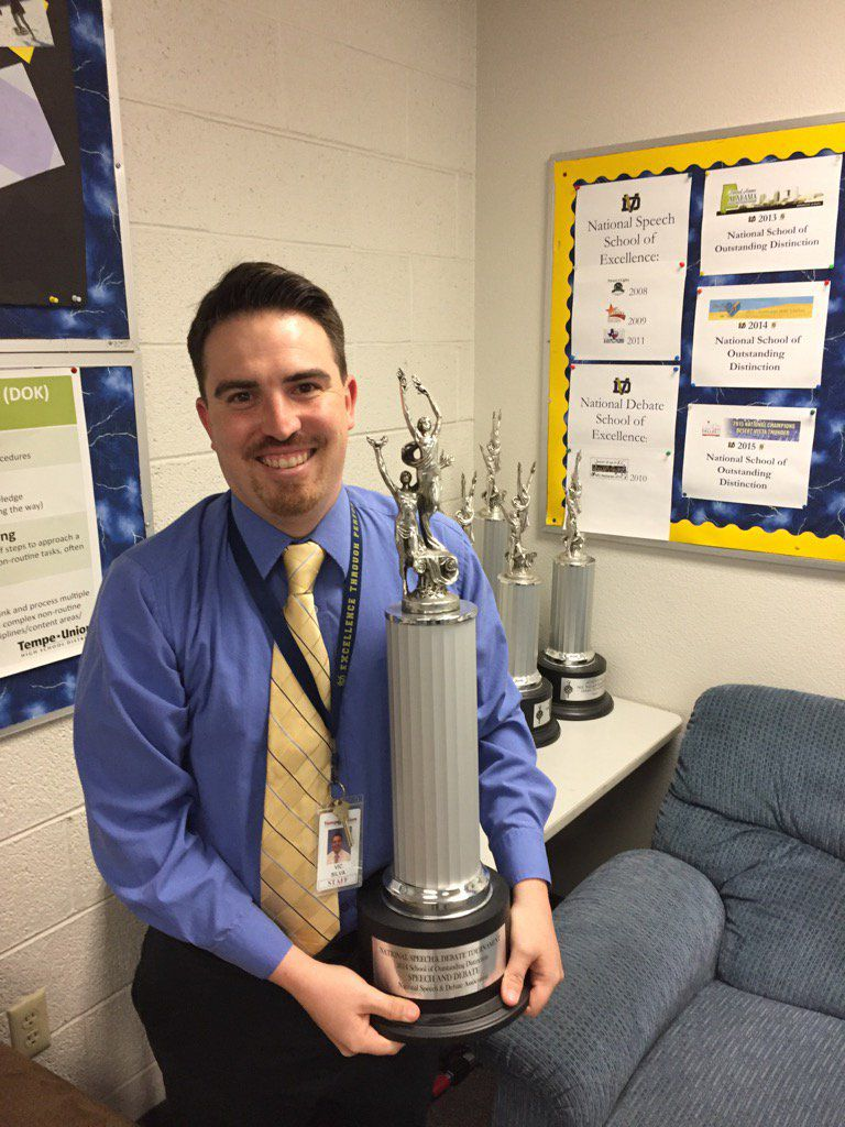 Victor Silva, a teacher and coach of Desert Vista High School's speech and debate team, holds one of the many trophies his students have won under his tutelage.