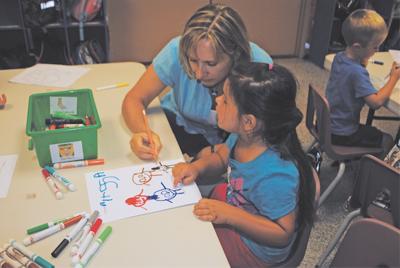 Teacher Cindy Garresh helps student Alyssa Hattula sketch with markers