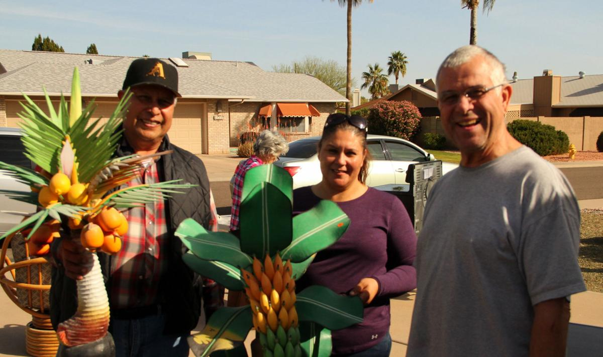 Manny Castillo and his daughter, Veronica, bought two carved wooden tropical fruit sculptures from Dennis Born, right, at his garage sale in Old Ahwatukee. Dennis lugged them back from the island of Martinique in 1999.
