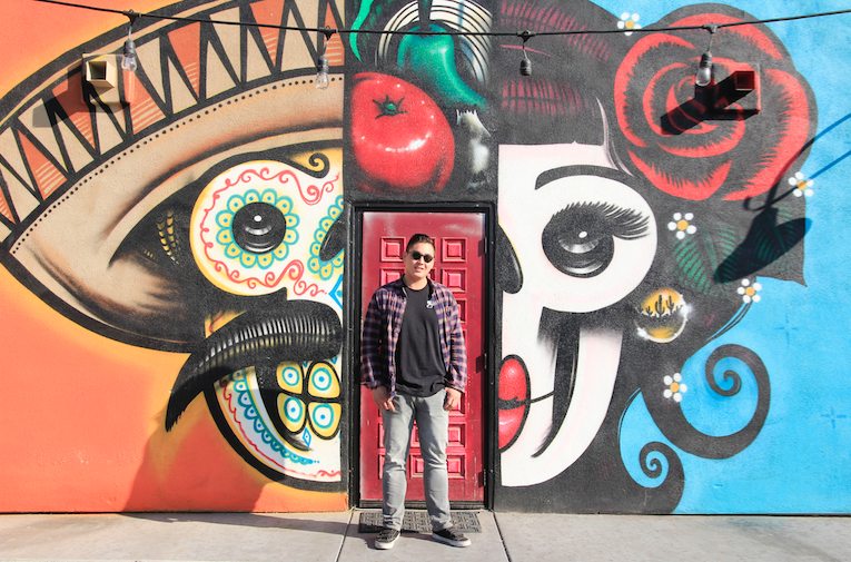 Christian Sciacca, majority owner of Ghett' Yo' Taco, stands in front of a mural on the front of the restaurant he owns. Lalo Cota painted the mural.