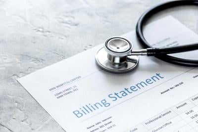 health care costs with billing statement, stethoscope on stone table