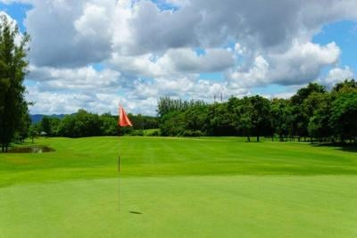 beautiful idyllic view of green with red flag and view of forest, blue sky with clouds.