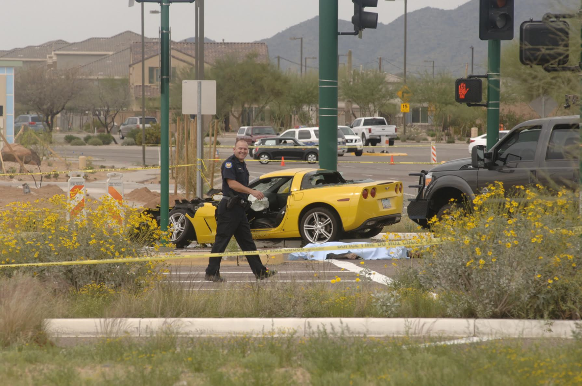 An unidentified officer passes by the Corvette that the suspect in an Ahwatukee killing stole and crashed in North Phoenix before he was fatally shot in a brief gun battle with officers.