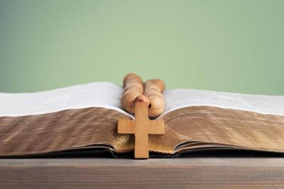 Rosary beads resting on open bible on