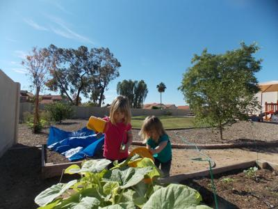 Kate and Brooke Van Cleve learn to tend a garden at Inspire Kids Montessori