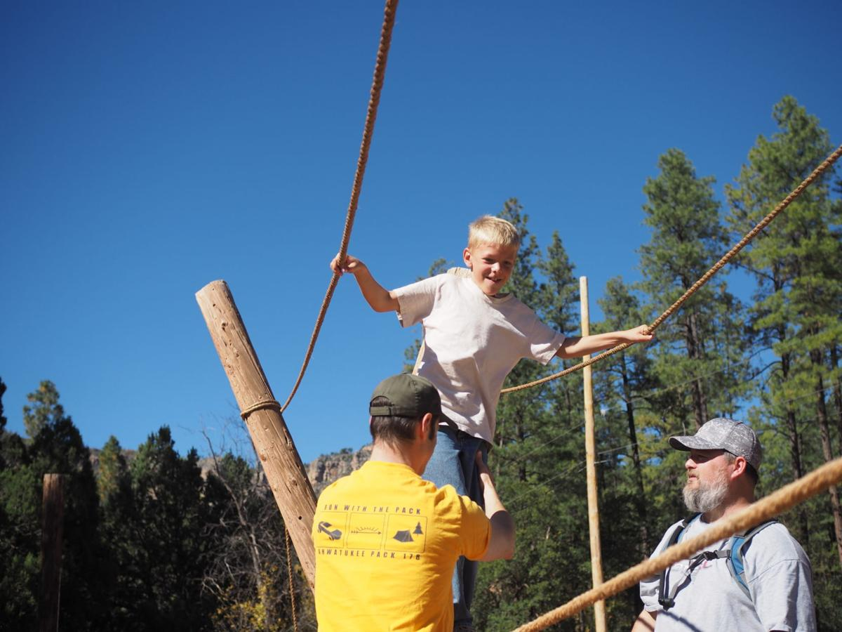 Helping 9-year-old Justin Madden on a rope course during Pack 178's trip to Payson are Marc Conkle, left, and Jim Neuman.