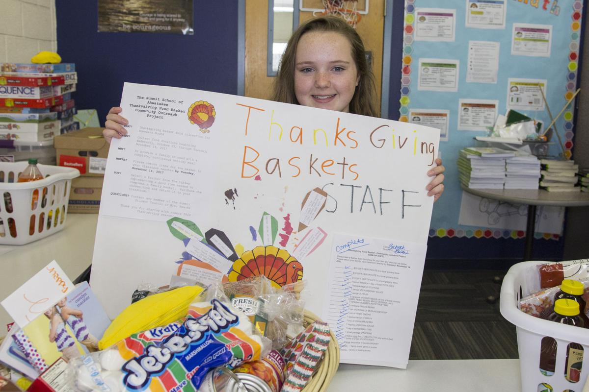 Annika Almquist shows the poster used in the holiday basket drive. Students grabbed feathers, each one containing the name a different item needed to make a Thanksgiving dinner.