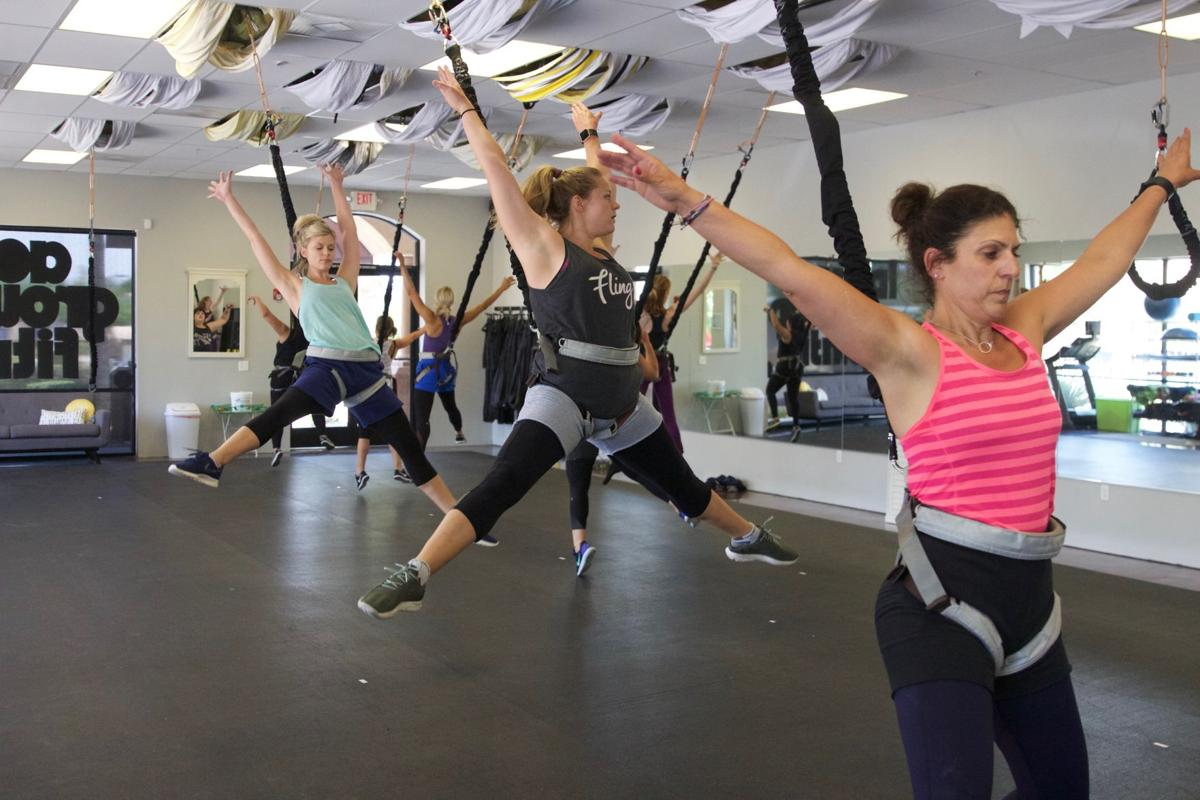 Participants in the bungee workout class at Tough Lotus in Chandler stretch in the air.
